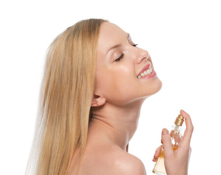 Smiling young woman applying perfume photo