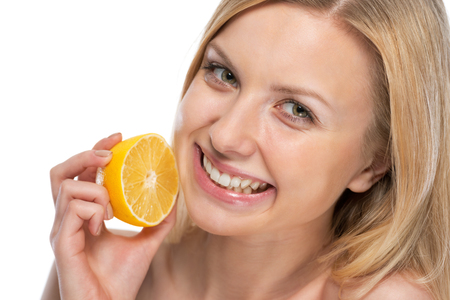 Portrait of smiling young woman with lemon