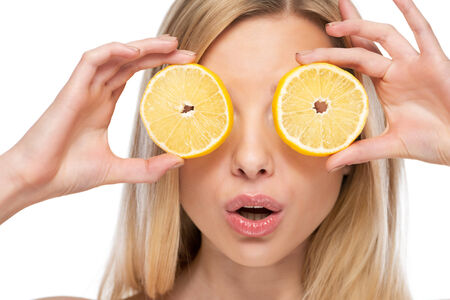 vitamin c: Young woman holding lemon slices in front of eyes Stock Photo