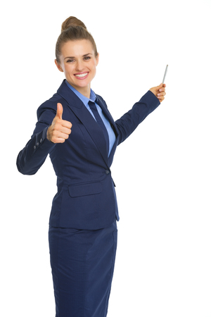 Smiling business woman pointing on copy space with pen and showing thumbs up photo