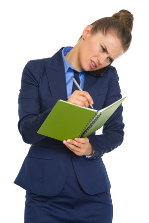 disquieted: Concerned business woman talking mobile phone and writing in notepad Stock Photo
