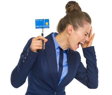 Frustrated business woman cutting credit card photo