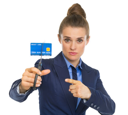Business woman pointing on credit card squeezed in scissors photo