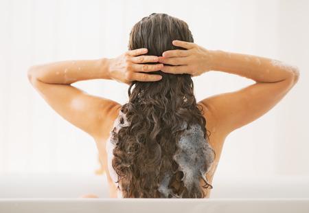champu: Lavar el cabello de la mujer joven. vista trasera