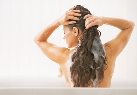 washing hair: Young woman washing hair. rear view