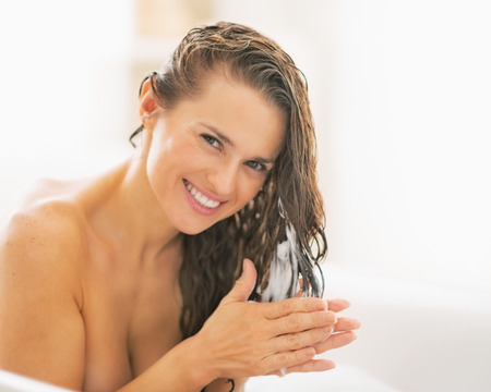 conditioner: Happy young woman applying hair conditioner Stock Photo