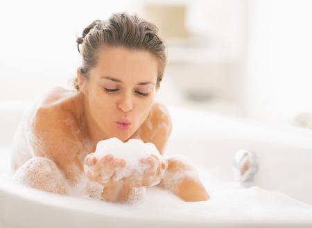 Jonge vrouw spelen met schuim in bad Stockfoto