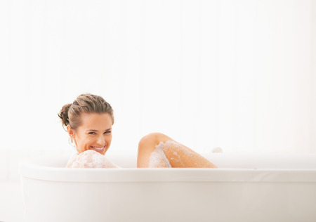 Happy young woman washing in bathtub