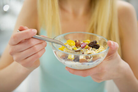 Closeup on young woman eating healthy breakfast photo
