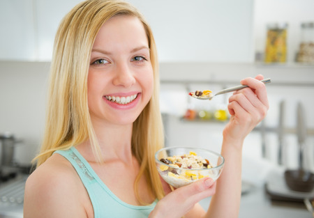 Happy young woman eating healthy breakfast photo