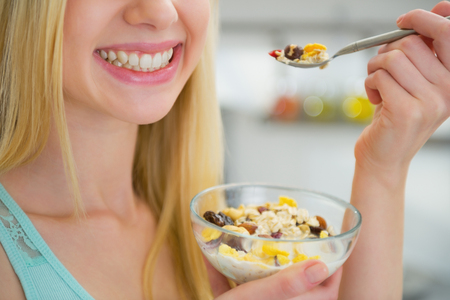 Closeup on happy young woman eating healthy breakfast photo