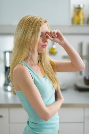 youthfulness: Young woman rubbing eyes after sleep in kitchen