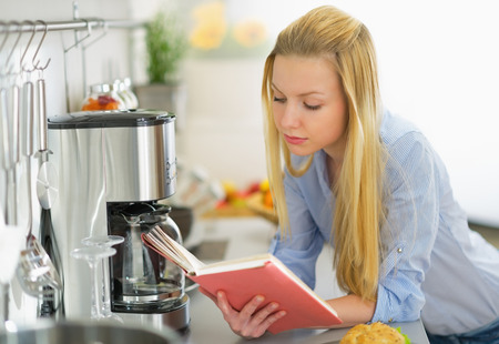 classbook: Young woman reading book in kitchen Stock Photo