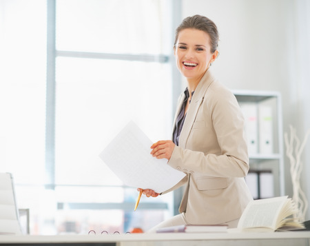 business costume: Happy business woman working in office with documents
