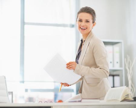 principal: Mujer de negocios feliz trabajando en la oficina con los documentos Foto de archivo