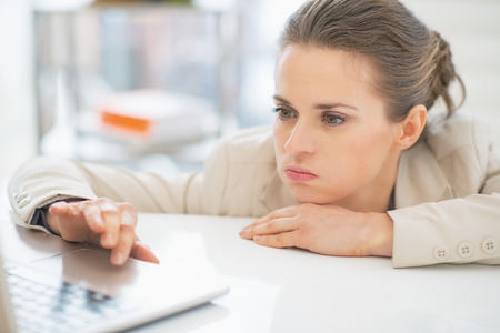 fiasco: Frustrated business woman working with laptop in office