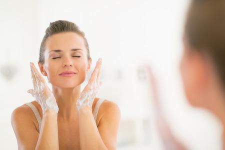 Jonge vrouw gezicht wassen in de badkamer