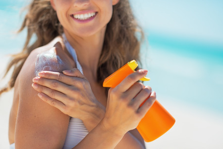 Closeup on smiling young woman with sun screen creme