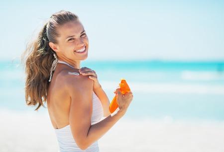 Sonriente mujer joven en playa de aplicar bloqueador solar crema Foto de archivo