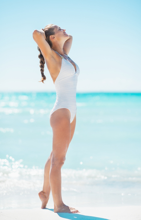 Happy young woman tanning on beach