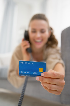 Closeup on happy young woman with credit card talking phone photo