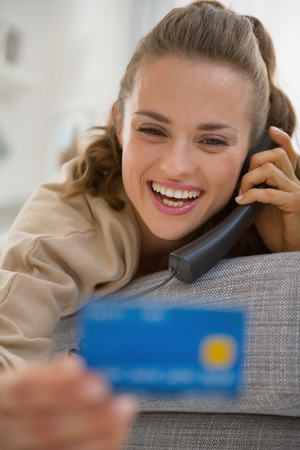 Happy young woman with credit card talking phone photo
