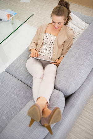 Happy young woman laying on sofa and using tablet pc photo