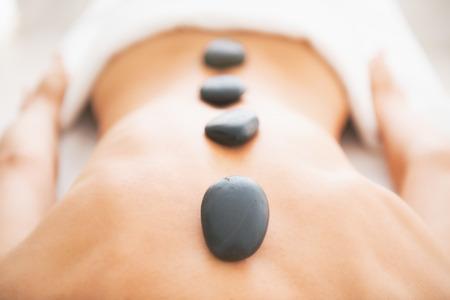 massage: Gros plan sur la jeune femme recevant massage aux pierres chaudes Banque d'images
