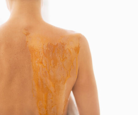 Closeup on young woman with back smeared in honey. rear view Stock Photo - 26854659