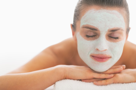 Young woman with revitalising mask on face laying on massage table