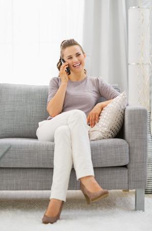 divan: Mujer joven feliz sentado en el div�n y hablando de tel�fono celular