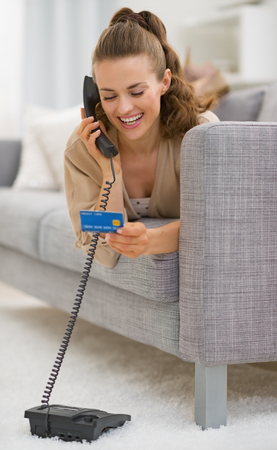 Happy young woman with credit card laying on sofa and talking phone photo