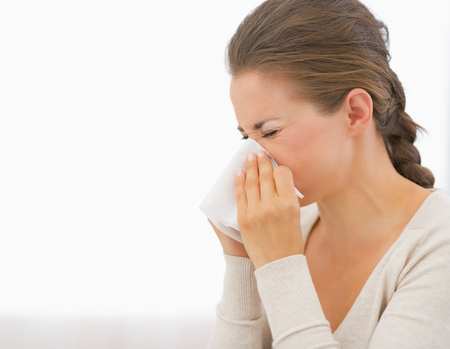 Portrait of young woman blowing nose Stock Photo - 26854768