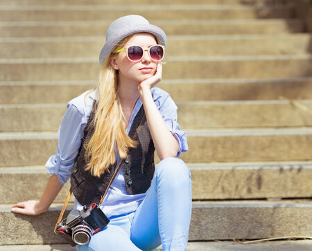 Young hipster sitting on stairs outdoors photo