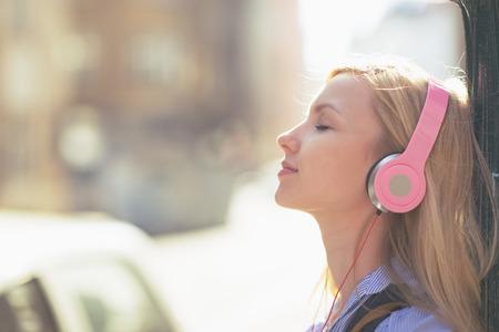 personas escuchando: Mujer joven escuchando música en los auriculares en la ciudad