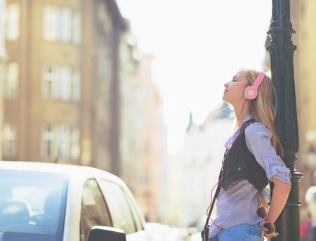 Relaxed jonge vrouw luisteren muziek in de koptelefoon in de stad