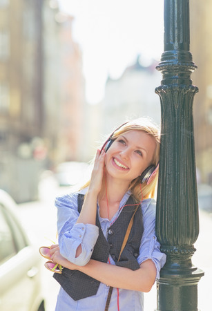 Happy young woman listening music in headphones in the city Stock Photo - 26977492