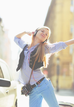 Cheerful young woman listening music in headphones in the city Stock Photo - 26977493