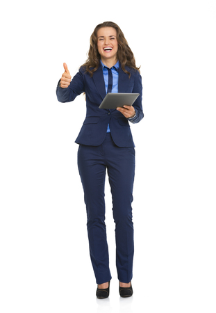 Full length portrait of smiling business woman with tablet pc showing thumbs up Stock Photo - 26977297