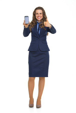 Full length portrait of business woman showing cell phone and thumbs up photo