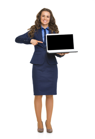 Full length portrait of happy business woman pointing on laptop blank screen Stock Photo - 26977312