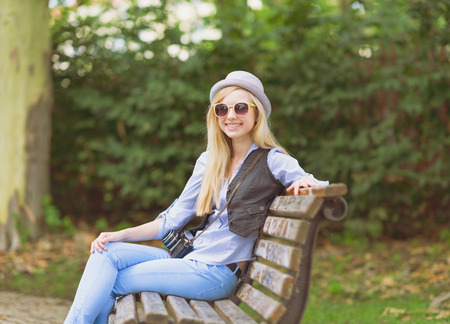Young hipster sitting on bench in the park Stock Photo - 26977537