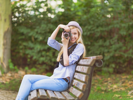 Young hipster taking photo with retro photo camera sitting on bench in the park Stock Photo - 26977538