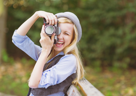 Young hipster taking photo with retro photo camera sitting on bench in the park Stock Photo - 26977539