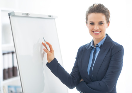 Portrait of happy business woman near flipchart Stock Photo