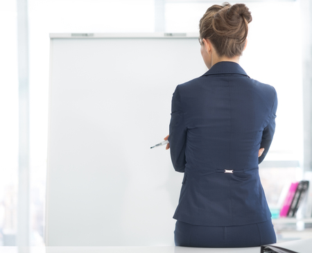 Thoughtful business woman standing near flipchart. rear view
