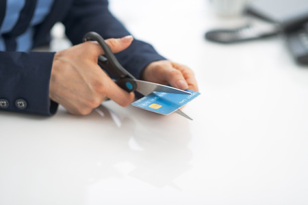 Closeup on business woman cutting credit card with scissors photo