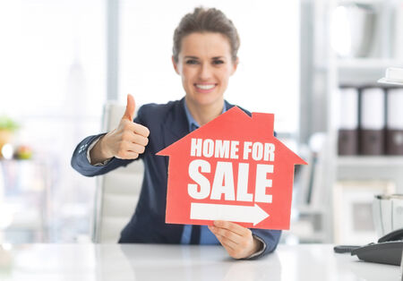 Happy realtor woman showing home for sale sign and thumbs up photo