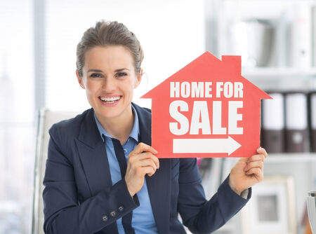 realtor: Happy realtor woman showing home for sale sign