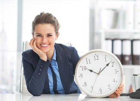 Mujer de negocios feliz que muestra el reloj